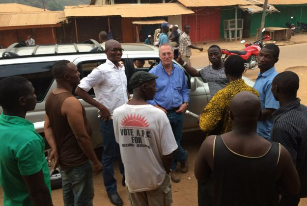Mark Doyle and Umaru Fofana (in white shirt) chatting with local people in Kabala, northern Sierra Leone