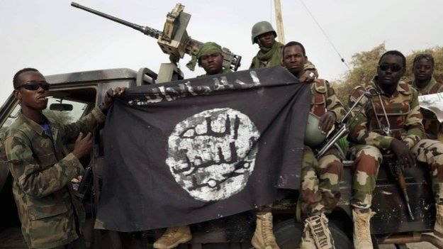 Soldiers from Niger with a Boko Haram flag after recapturing Damasak