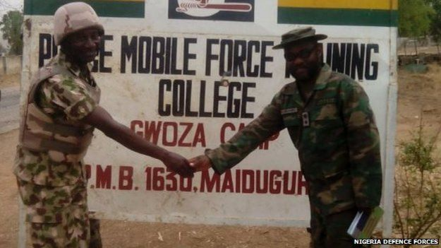 Army personnel shaking hands in front of a police training college near Gwoza