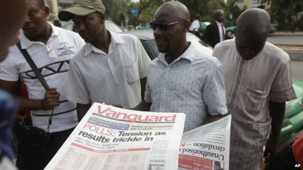 People read newspapers with election headlines on the street in Abuja, Nigeria Monday, March 30, 2015