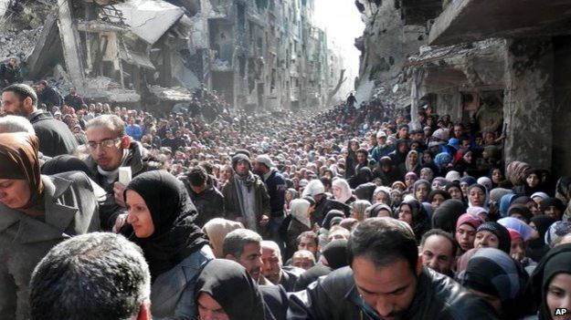 File photo: Residents of the besieged Palestinian camp of Yarmouk queue to receive food supplies in Damascus, Syria, 31 January 2014