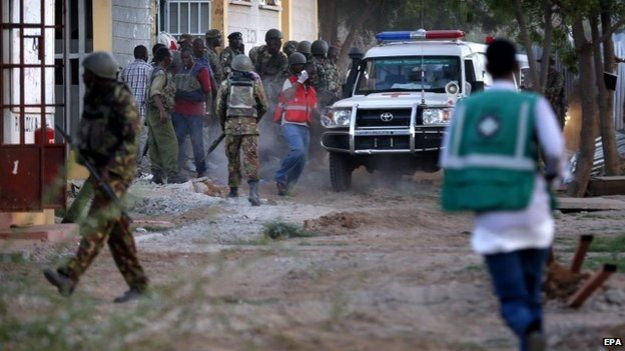 Kenyan soldiers and ambulance workers run as they prepare to evacuate students