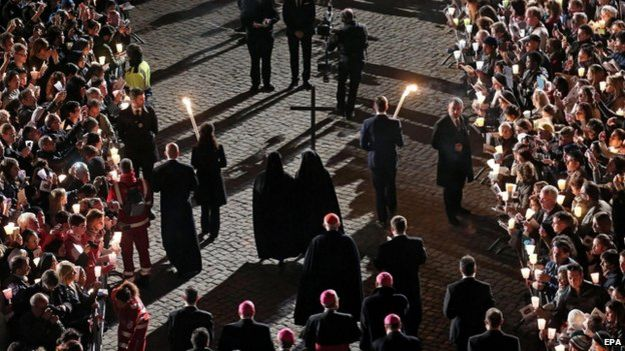 Nuns hold the cross during a station of the Via Crucis (Way of the Cross) torchlight procession celebrated by Pope Francis in front of the Colosseum on Good Friday, in Rome
