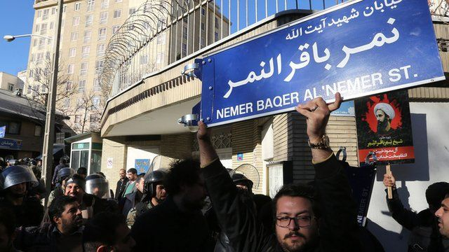 An Iranian holds a street sign bearing the name of Shia cleric Nimr al-Nimr during a demonstration against his execution by Saudi authorities