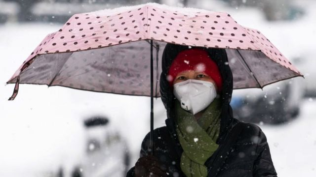 A woman wears a medical mask during a snowfall in a street in February, 2020
