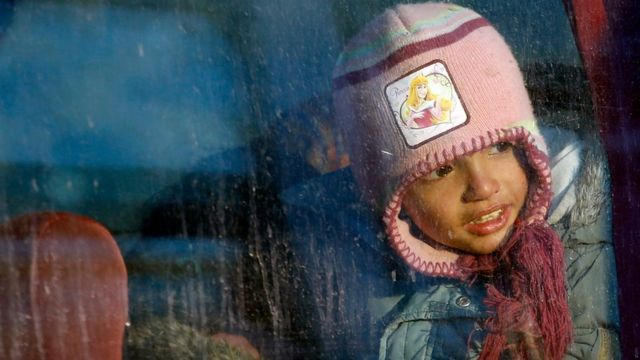 A migrant girl looking through a bus window in the makeshift refugee camp at the northern Greek border point of Idomeni, Greece, Friday, 25 March 2016.