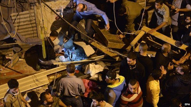 Residents inspect damage caused by two suicide attacks