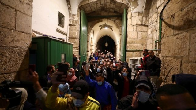 Worshippers, some wearing masks, hold up their mobile phones while entering the compound housing the Al-Aqsa Mosque