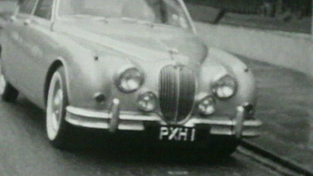 Black and white still from footage shows a car