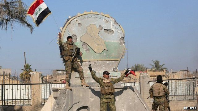 A member of the Iraqi security forces holds an Iraqi flag in the city of Ramadi