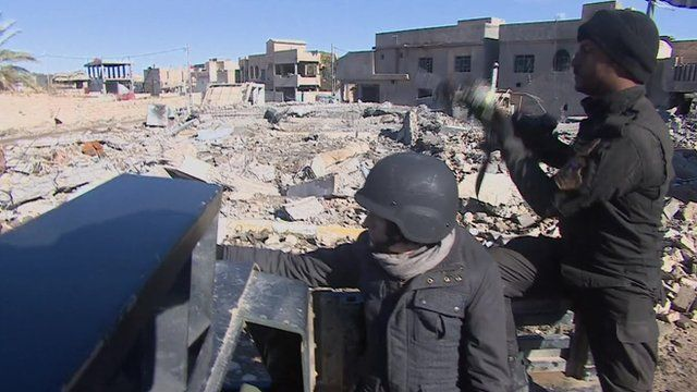 Thomas Fessy with Iraqi soldier driving through Ramadi looking at rubble