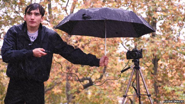 A man, wet from the falling rain, stands next to a camera on a tripod that is under an umbrella