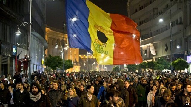 Large flag and crowds of protesters in Calea Victoriei