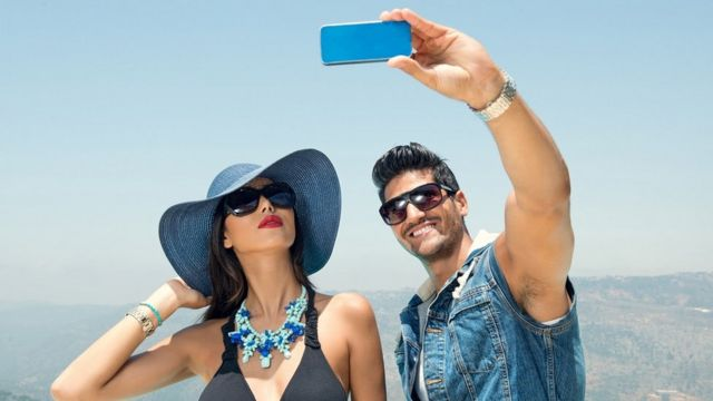 Man in sunglasses posing for a selfie in a sunny location with a lady in a a sunhat and bright red lipstick