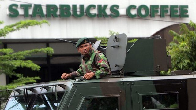 An Indonesian soldier on guard in an armoured vehicle after a bomb blast in front of a Stabucks in Jakarta, Indonesia, 14 January 2016.