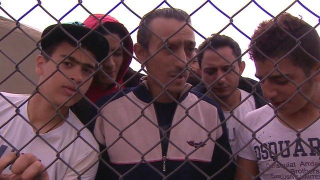 Ibrahim Maarouf (c) and other migrants behind a wire fence at military base in Dhekelia