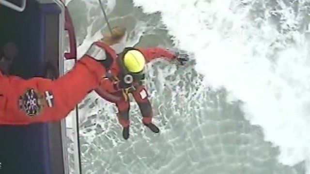A rescuer descends from a helicopter