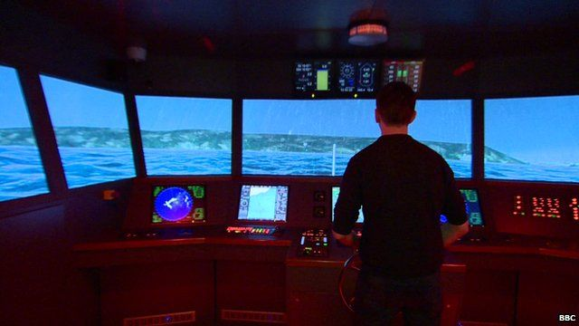 Man standing in front a computer screen with an image of a storm. There are also control buttons that resemble controls found on a ship