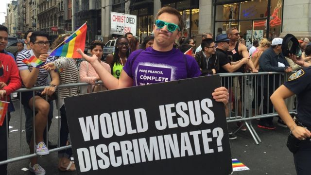 """A protestor with a signing saying """"Would Jesus discriminate?"""""""