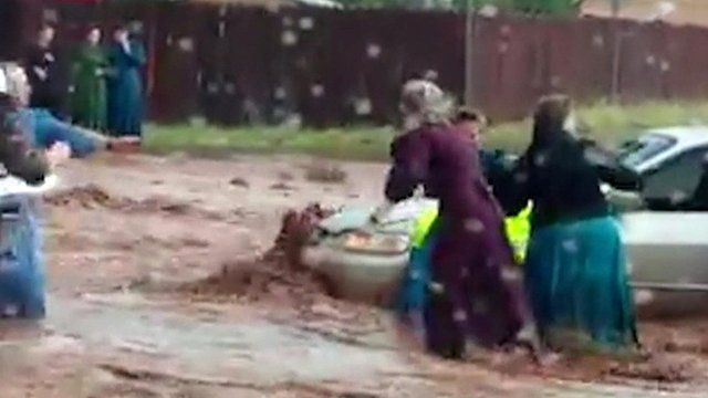 People struggle through flood water