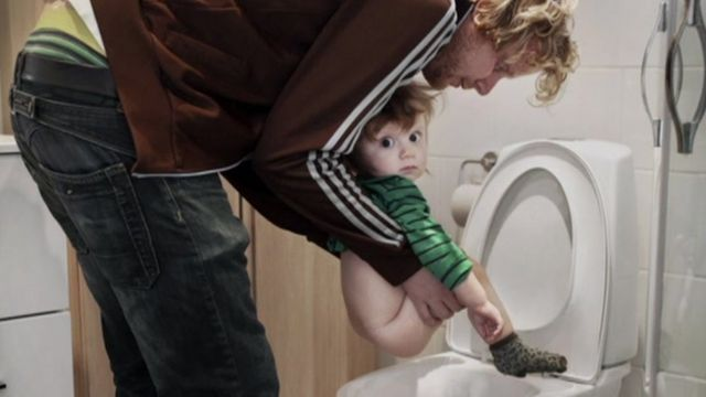 Man holding child over loo