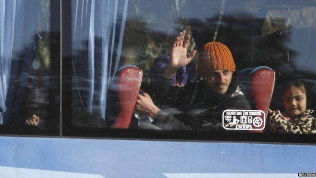 A man waves from the window of a bus