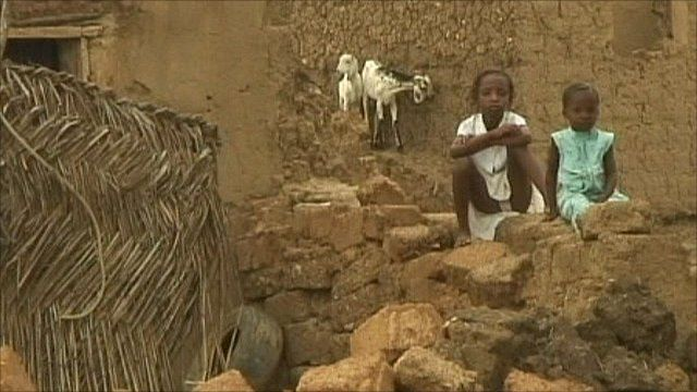 Children sit in the ruins of a village