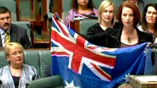 Julia Gillard holds up an Australian flag