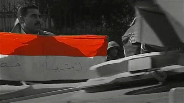 Protester with flag and passing tank