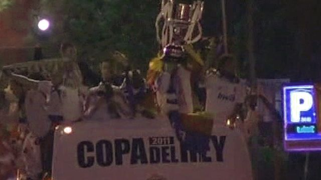 Players hold trophy on open top bus in Madrid