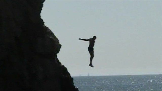 A person jumping off a cliff into water