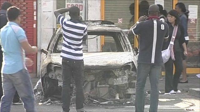 People taking photographs of a burnt-out car