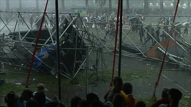 Festival-goers sheltering from rain in front of collapsed rigging towers