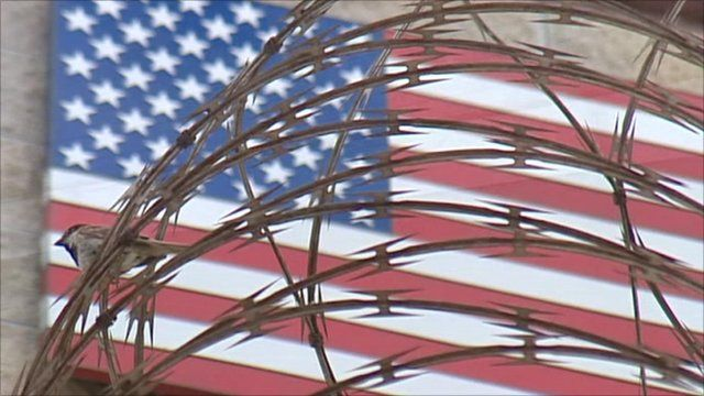 American flag behind wire fence at Guantanamo Bay