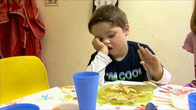 Boy eating his dinner at a table