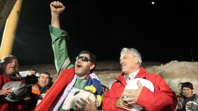 Luis Urzua (L) is greeted by President Sebastian Pinera