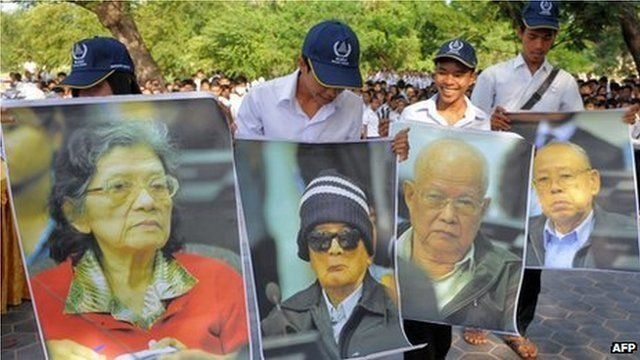 Cambodian students hold up posters of former Khmer Rouge leaders