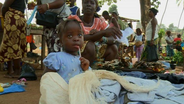 Little girl with mother and other women at a community clinic in Sierra Leone's Freetown
