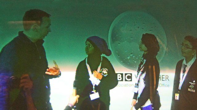 The students are superimposed on a chroma key screen in the BBC Weather studio