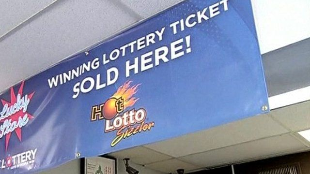 """Banner in shop which says """"winning lottery ticket sold here""""."""