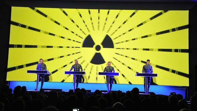 The band Kraftwerk performs in front of an atomic radiation symbol