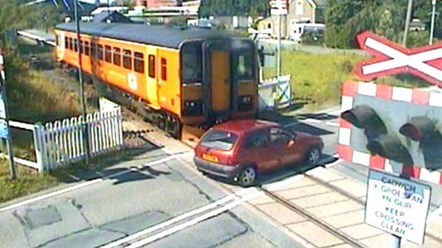 Car narrowly misses a train at a level crossing