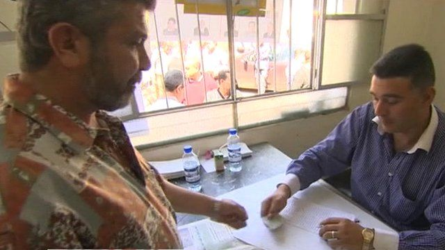Man collecting voting papers in Syria