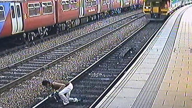 Still of CCTV footage of woman on rail tracks