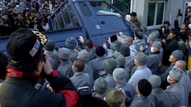 Rioting monks turn over a van