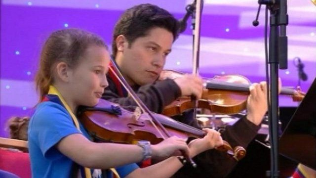 Young girl and an older boy play violins