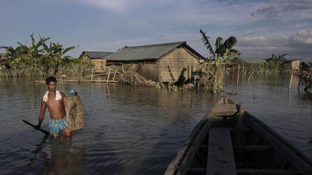 An Indian villager wades through flood waters at Gagalmari village in Assam state