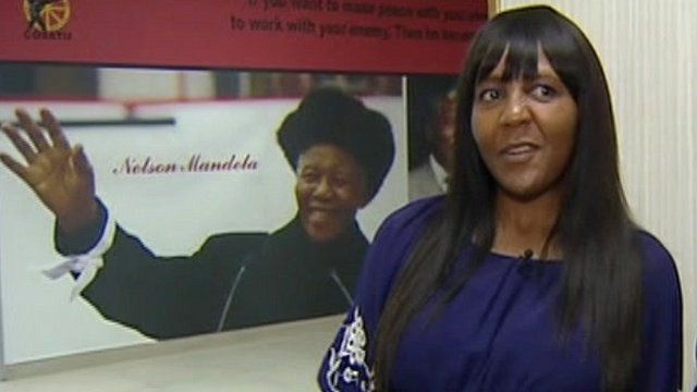 Ndileka Mandela in front of picture of Nelson Mandela