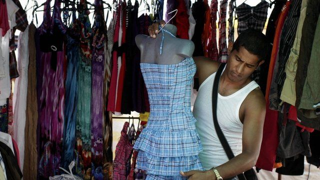 A stall owner in Cuba dresses a mannequin