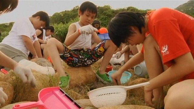 Local residents gathering pellets on a beach